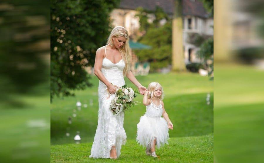 Jessica Simpson wearing a white dress walking through the grass at Ashlee Simpsons wedding
