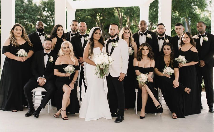 Selena Gomez sitting surrounding the bride and groom in a black off the shoulder bridesmaids dress