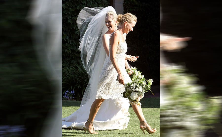 Naomi Watts walking with the bride wearing a short white lace dress