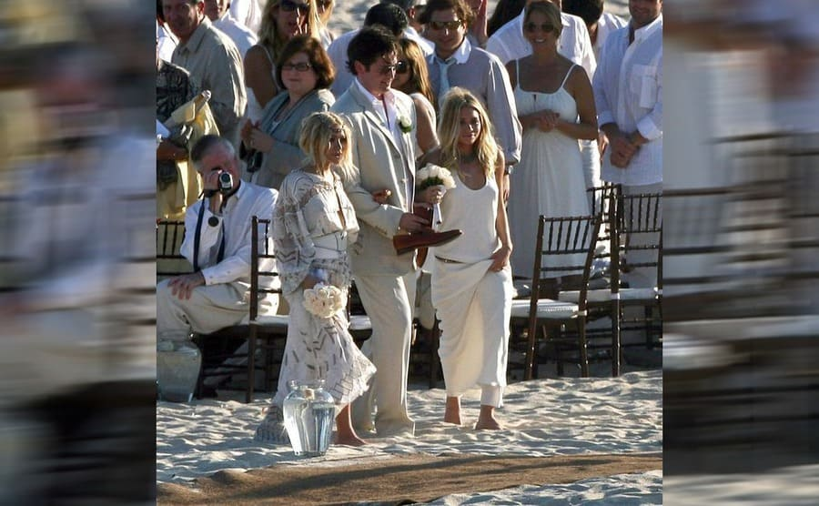 Mary Kate and Ashley walking down the aisle as bridesmaids with a guy