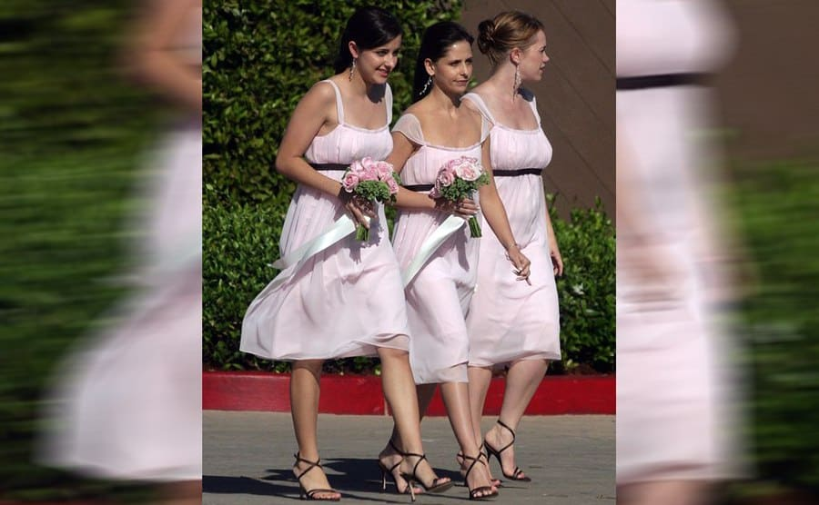 Sarah Michelle Gellar with two other bridesmaids walking in a parking lot