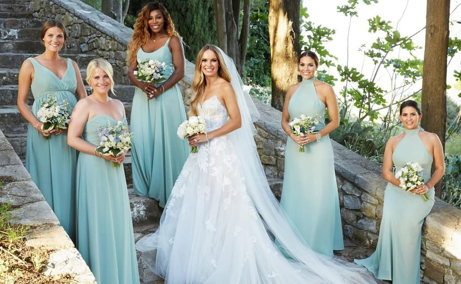 Serena Williams with other bridesmaids surrounding the bride on stone-paved steps