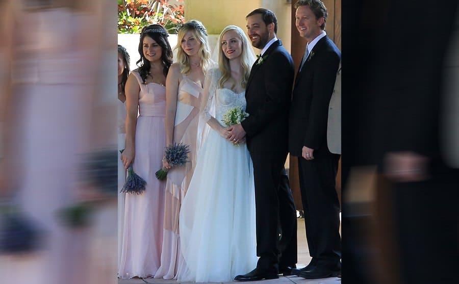 Kirsten Dunst standing next to the bride and groom
