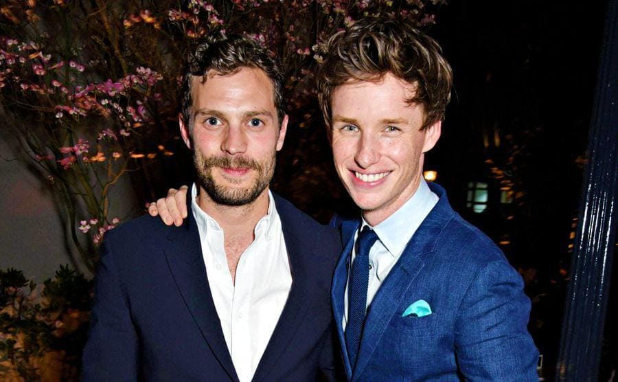 Eddie Redmayne and Jamie Dornan posing on a grey brick street