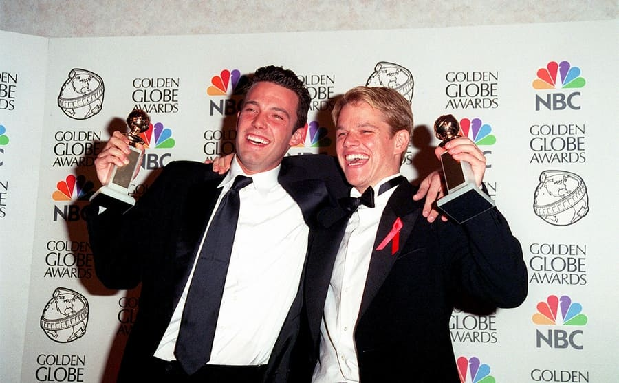 Ben Affleck and Matt Damon on the red carpet holding their Golden Globe awards in 1998