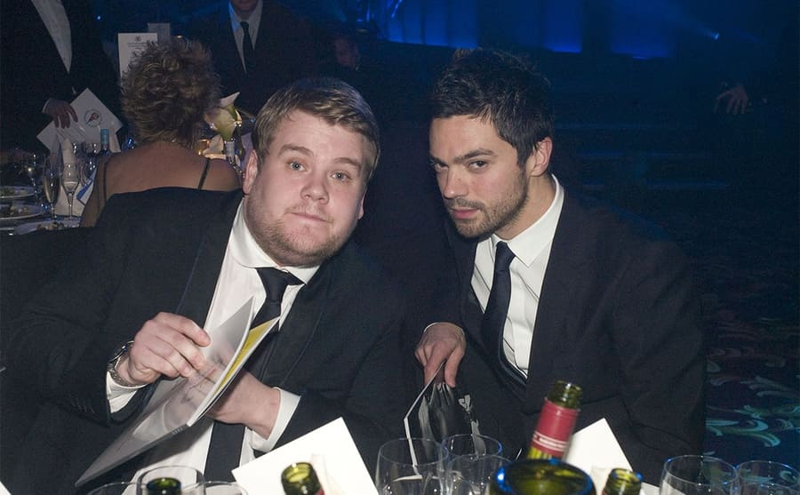 James Corden and Dominic Cooper sitting at a dinner table at an event in 2009