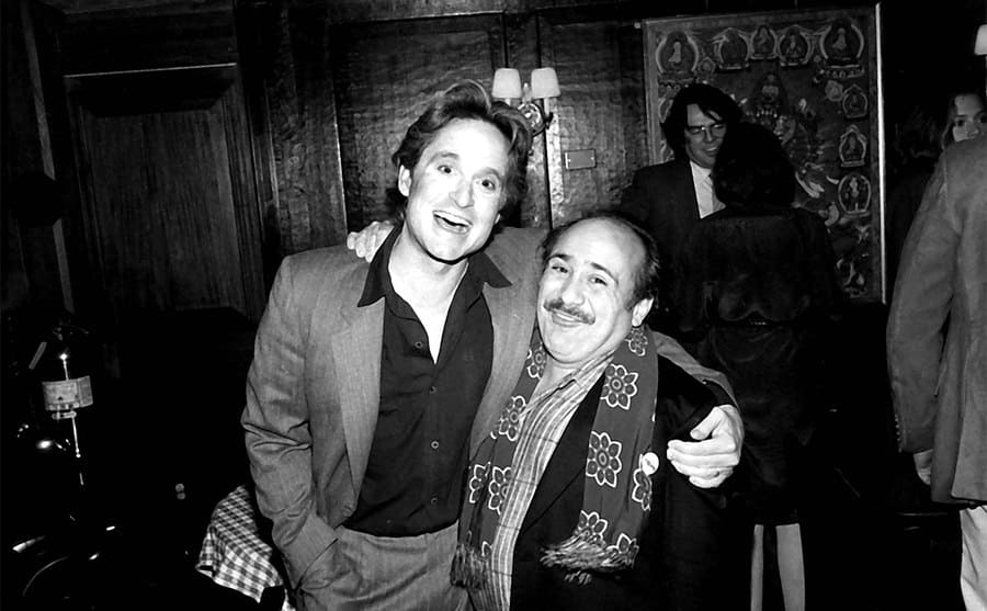 Michael Douglas and Danny DeVito posing together at an event