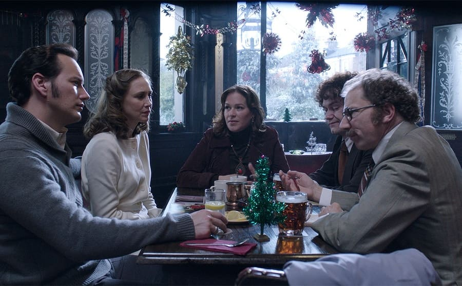 Patrick Wilson, Vera Farmiga, Franka Potente, Simon McBurney, and another man sitting around a table at a bar drinking in The Conjuring 2