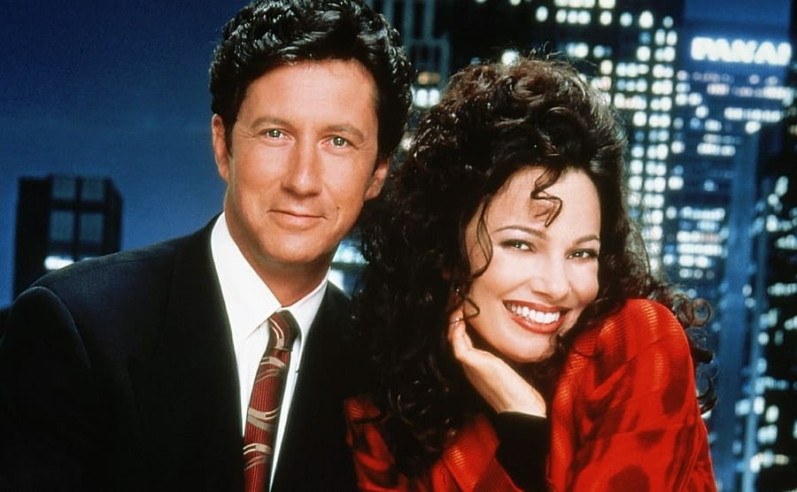 Charles Shaughnessy and Fran Drescher posing together with a skyline backdrop