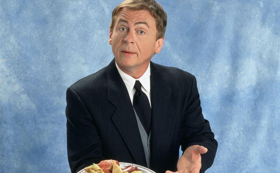 Daniel Davis on a blue background offering a platter of appetizers
