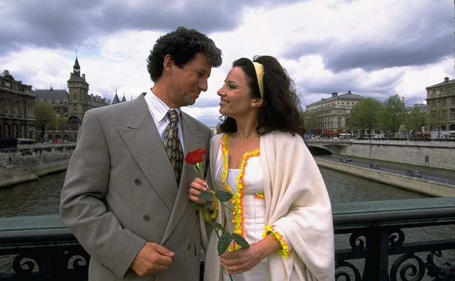 Charles Shaughnessy and Fran Drescher holding a rose on a bridge in the show The Nanny
