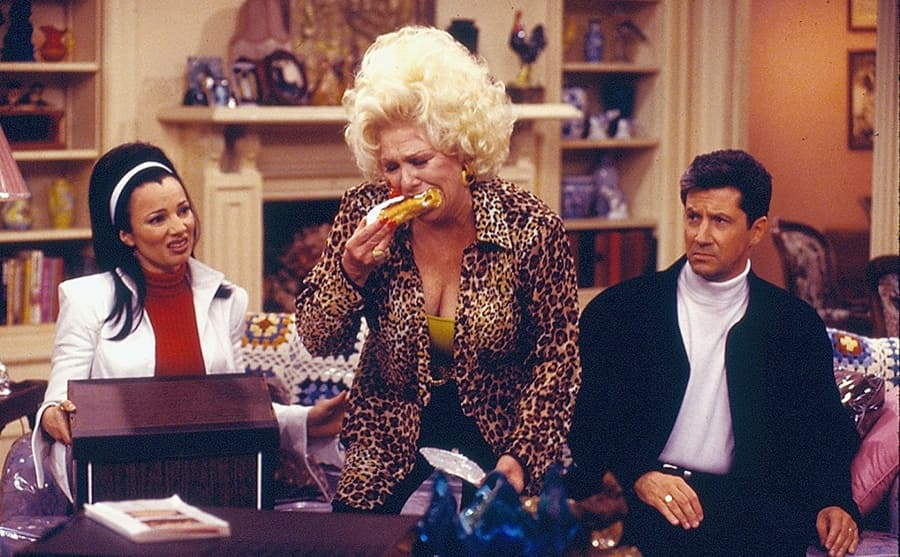 Fran Drescher, Renee Taylor, and Charles Shaughnessy sitting on a couch while Renee Taylor eats corn