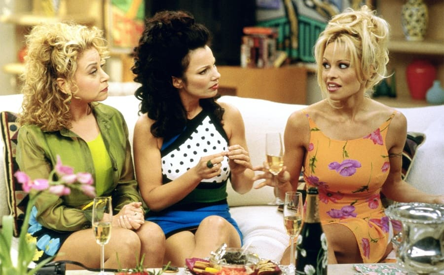 Rachel Chagall, Fran Drescher, and Pamela Anderson gossiping on the couch with champagne and snacks