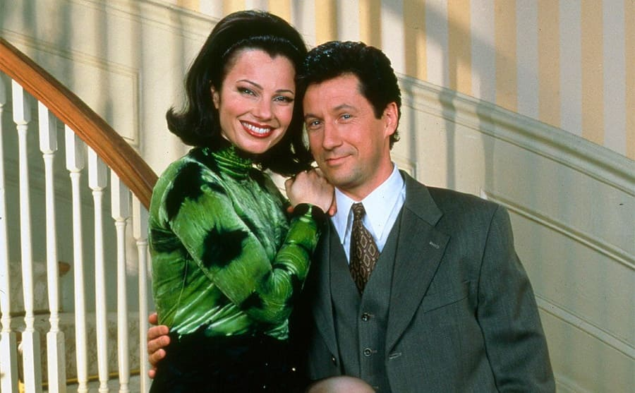 Fran Drescher and Charles Shaughnessy posing on the banister on The Nanny