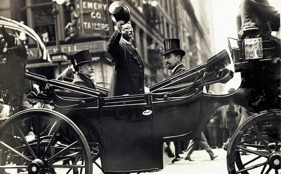Theodore Roosevelt standing in a carriage tipping his hat while Mayor William Gaynor and Cornelius Vanderbilt are seated