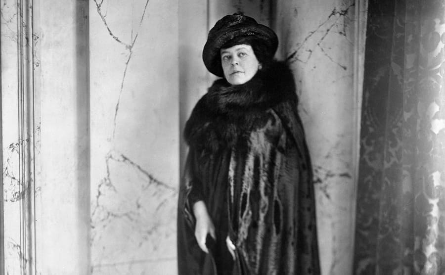 Alva Vanderbilt dressed in expensive clothing, posing in a marble entryway