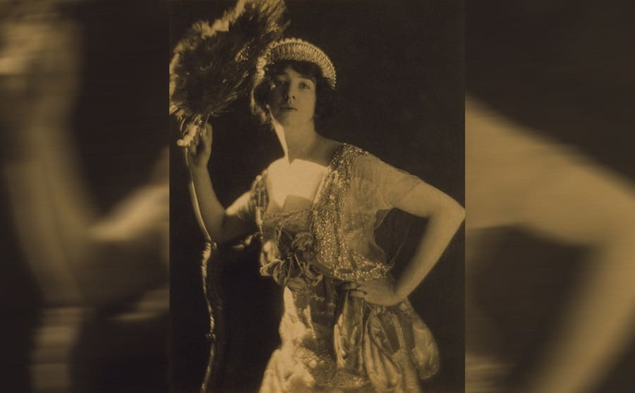 Gertrude Vanderbilt Whitney posing with a feather
