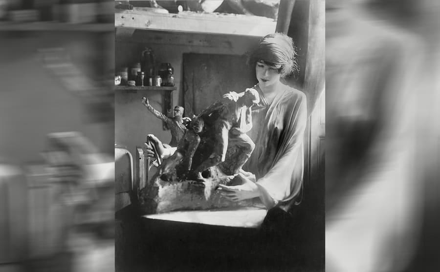 Gertrude Vanderbilt Whitney sculpting in an art studio