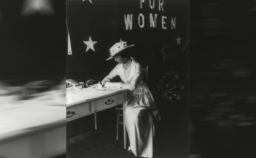 Consuelo Vanderbilt sitting at a table with the bottom of a sign behind her reading 'for women'