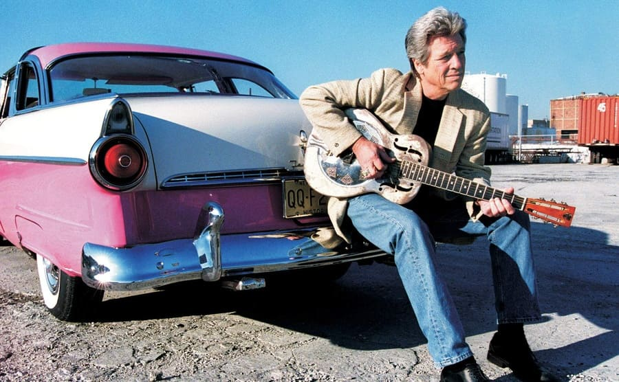 John P. Hammond with a guitar leaning against the back of a pink and white car