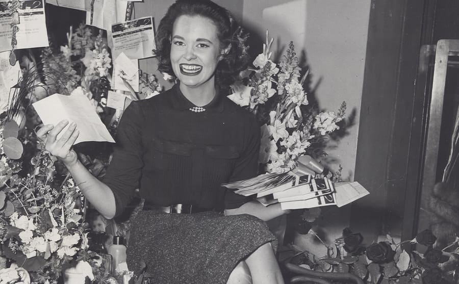 Gloria Vanderbilt posing sitting on a desk with her hands full of papers and flowers surrounding her
