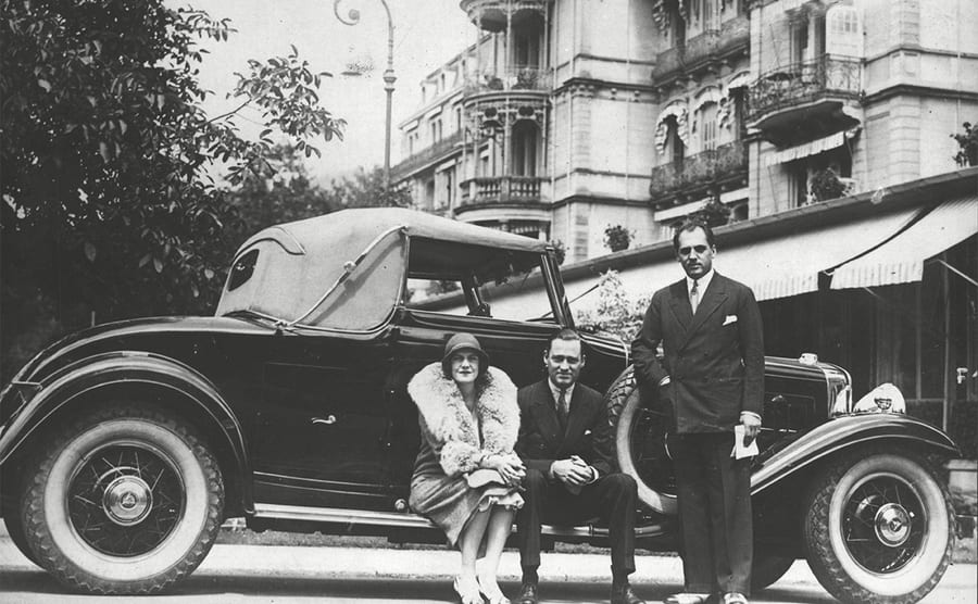 Mr. and Mrs. William H Vanderbilt and Mr. Kurt Brenner posing next to their car in front of Hotel Stephanie in Germany