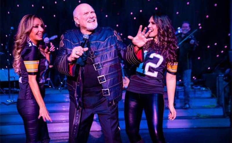 Terry Bradshaw on stage with two women in football jerseys