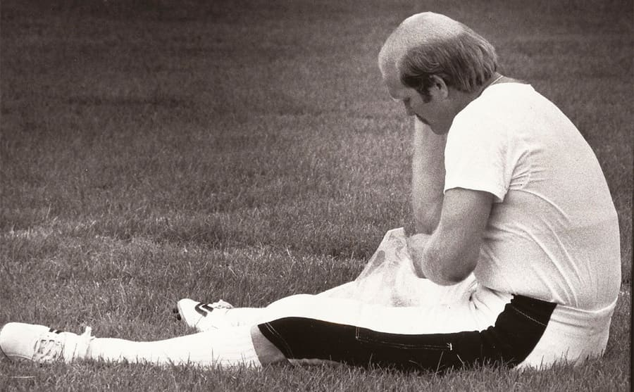 Terry Bradshaw on the field holding his elbow
