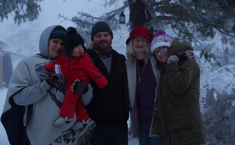 Noah, Rhain, Ami, Baby Eli, and another daughter posing in the snow covered wilderness