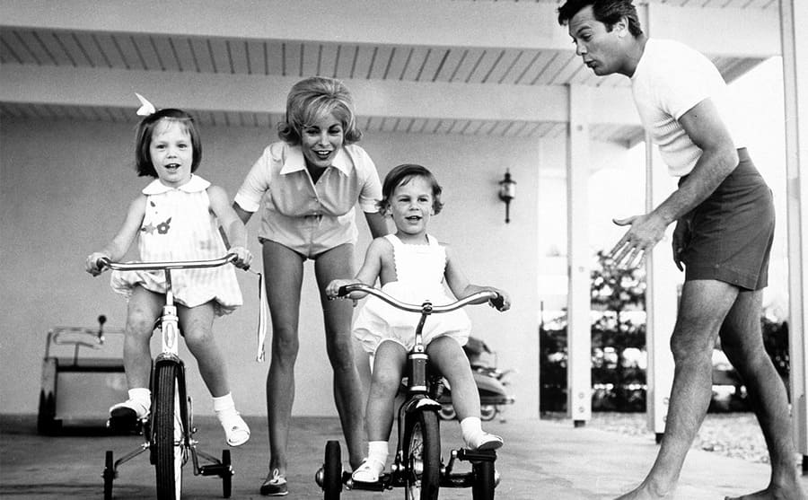 Janet Leigh and Tony Curtis with their daughters Kelly and Jamie Lee riding tricycles