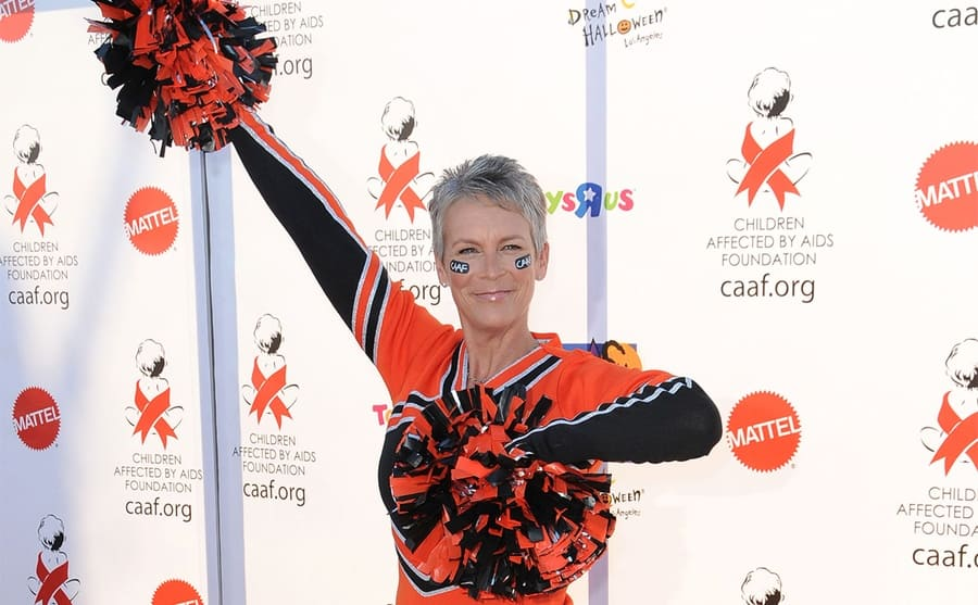 Jamie Lee Curtis in an orange and black cheer uniform with pompoms