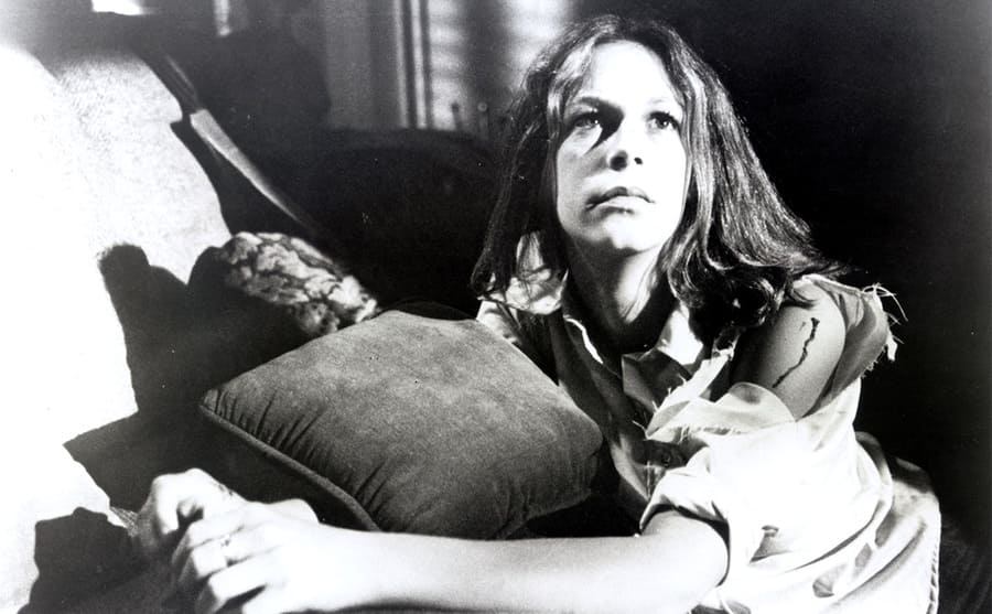 Jamie Lee Curtis kneeling next to a couch in the film Halloween