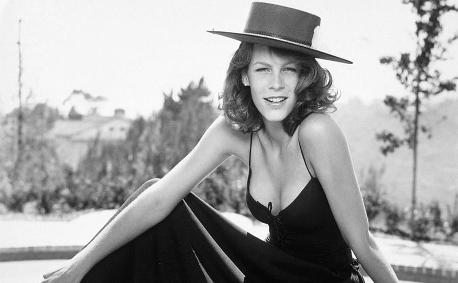 Jamie Lee Curtis posing with a hat on in front of a pool circa 1977