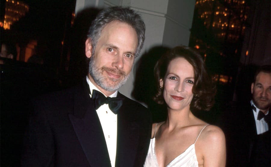 Christopher Guest and Jamie Lee Curtis posing on the red carpet at the Golden Globe Awards 1995