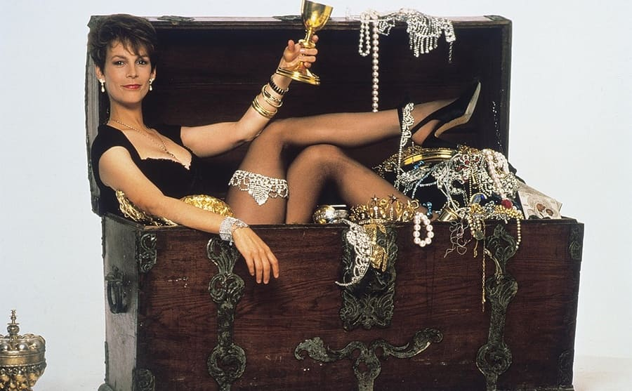 Jamie Lee Curtis in an old wooden trunk full of jewelry and gold from the film A Fish Called Wanda