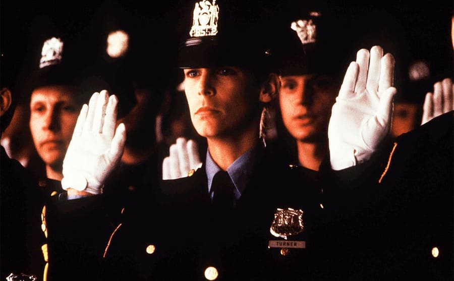 Jamie Lee Curtis in a police uniform with her right hand raised