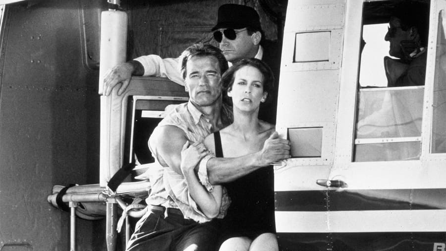 Arnold Schwarzenegger and Jamie Lee Curtis sitting on the edge of a helicopter in the film True Lies