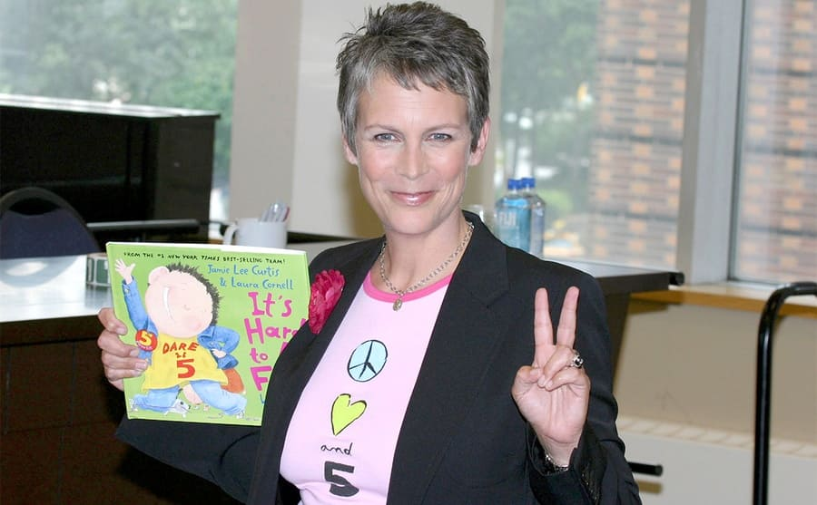 Jamie Lee Curtis holding up one of her books