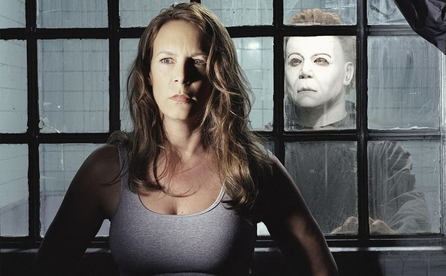 Jamie Lee Curtis standing with her back to a window with a man wearing a mask