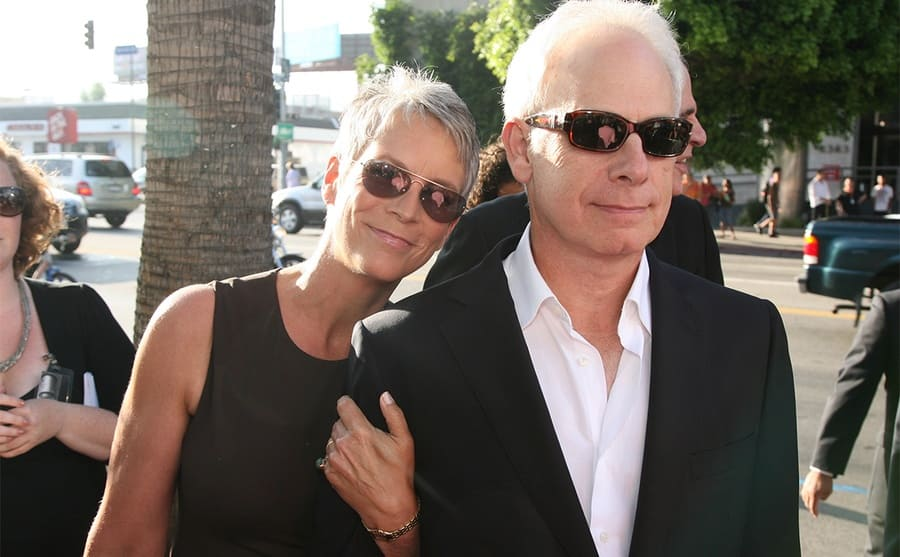 Jamie Lee Curtis holding on to her husbands' arm on the way to a movie premiere