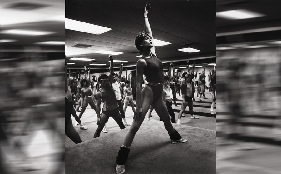 Jamie Lee Curtis running an aerobics class in a leotard in a scene from Perfect 1985