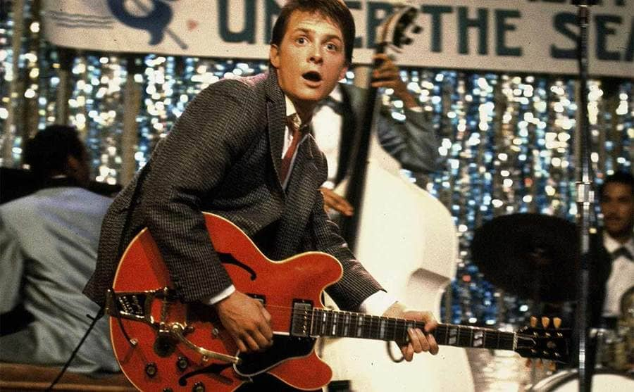Michael J Fox playing the guitar on stage in a scene from Back to the Future