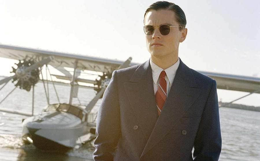 Leonardo DiCaprio standing on the beach with his plane in the water behind him