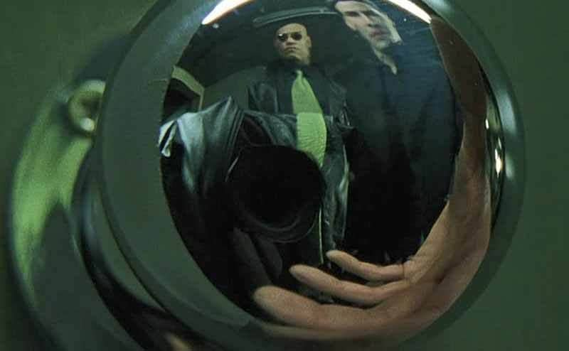 A scene from The Matrix of people's reflection in a doorknob along with the reflection of the video camera