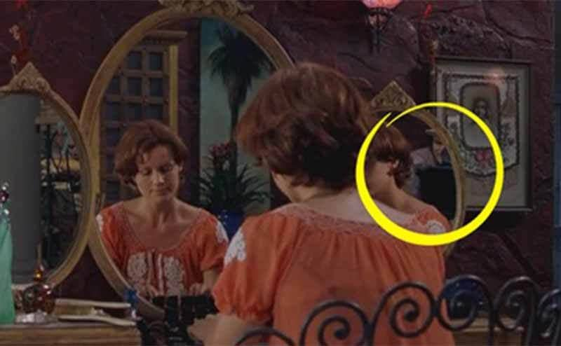 Someone sitting at a makeup table in the film Spy Kids with the cameraman visible from the tri-fold mirror
