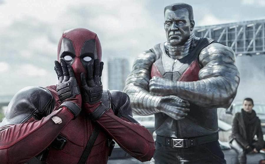 Ryan Reynolds standing shocked with Stefan Kapicic and Brianna Hildebrand behind him in a scene from Deadpool
