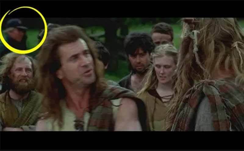 The scene from Braveheart with everyone speaking out in the open with a camera man walking behind them wearing a baseball cap