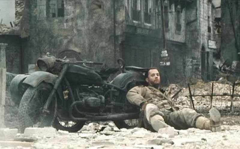 Tom Hanks leaning on a motorcycle in the film Saving Private Ryan
