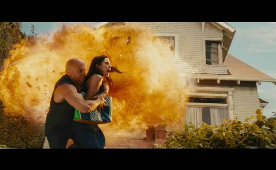 Vin Diesel pushing Jordana Brewster out of the way while a house explodes behind them