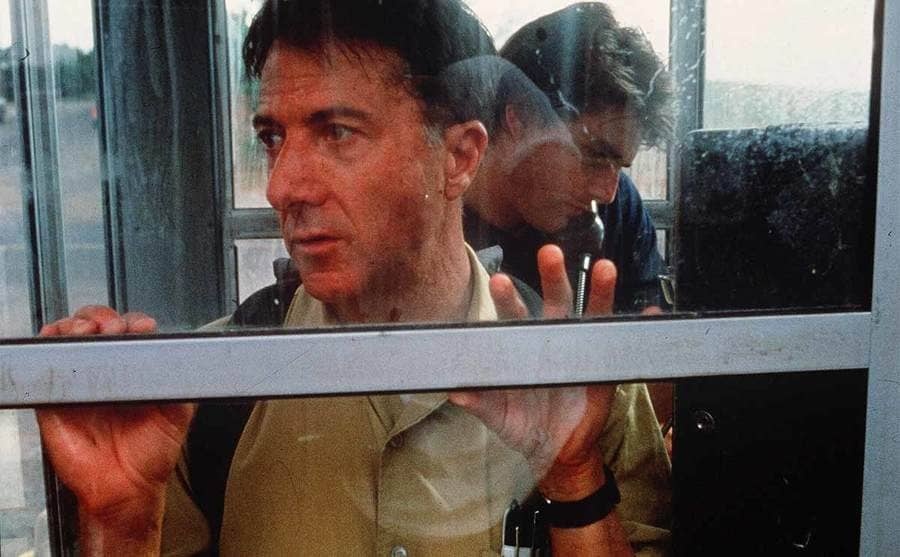 Dustin Hoffman looking out of the phone booth while Tom Cruise makes a call in the film Rain Man